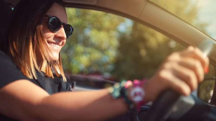 Smiling young woman driving a car.