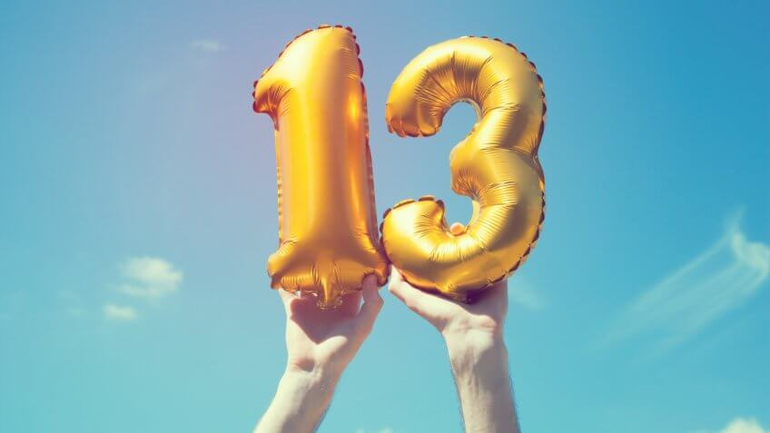 A gold foil number 13 balloon is held high in the air by caucasian male hand.