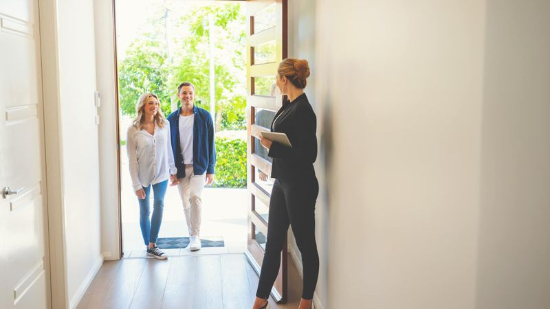 Real estate agent showing a young couple a new house.