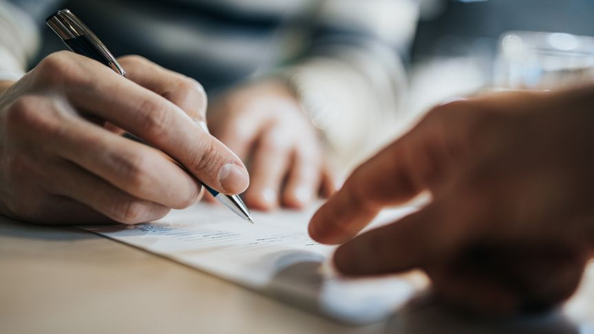 Close up of unrecognizable man signing a contract while financial advisor is aiming at the place he need to sign.