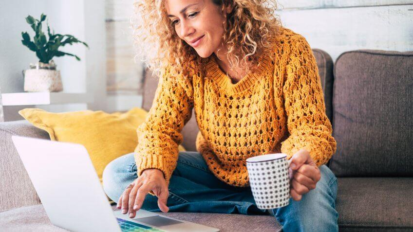 Nice beautiful lady with blonde curly hair work at the notebook sit down on the sofa at home - check on line shops for cyber monday sales - technology woman concept for alternative office freelance.