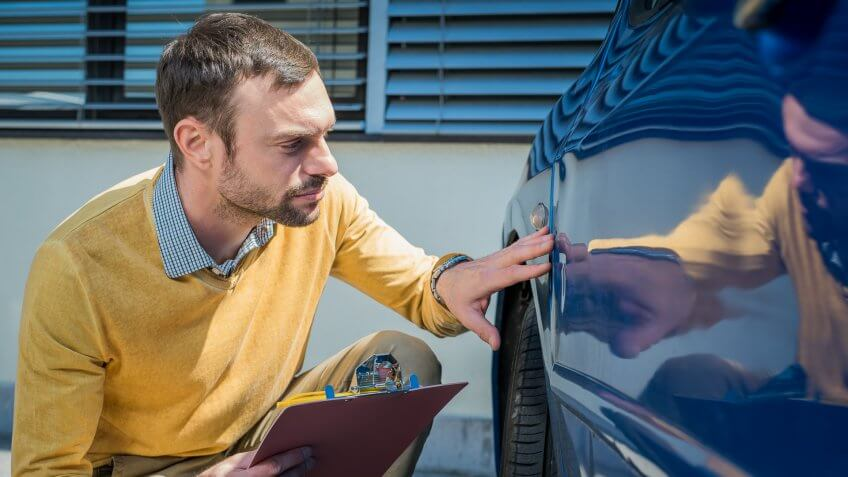Insurance agent inspects a car after accident.