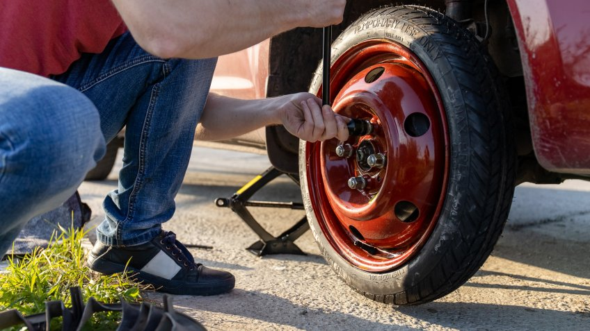 man changing tire to spare