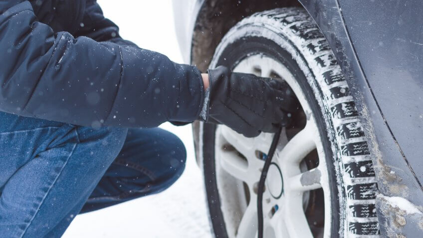 man inflating winter tires