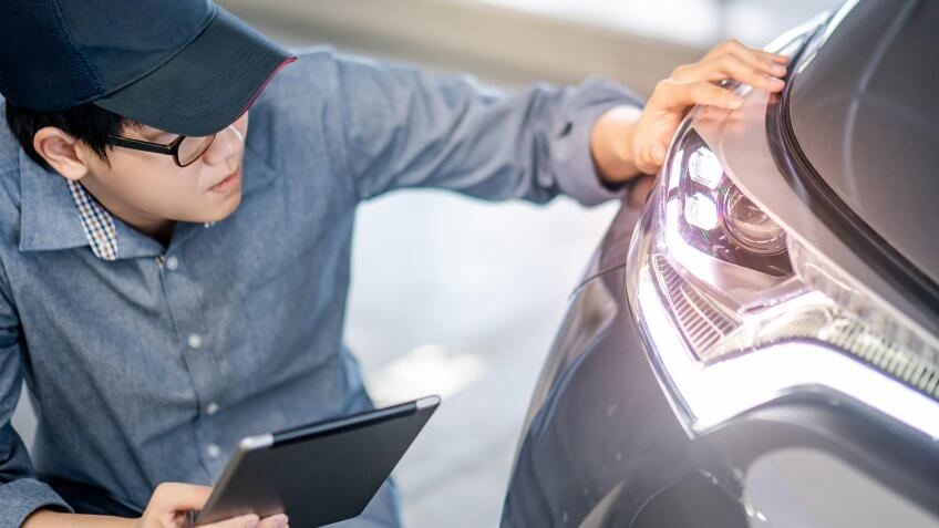 Young Asian auto mechanic holding digital tablet checking headlight in auto service garage.