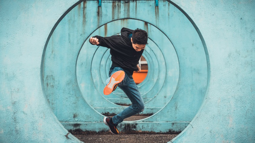 Young Asian active man in action of jumping and kicking, circle looping wall background.