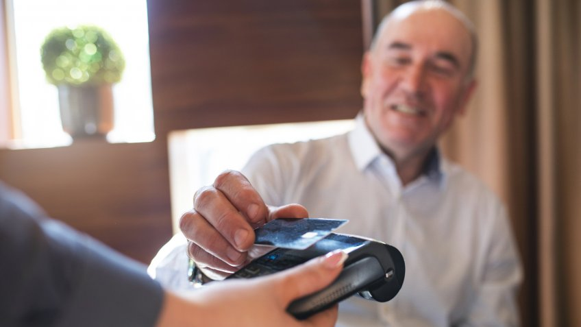 Cheerful senior businessman paying with a credit card.