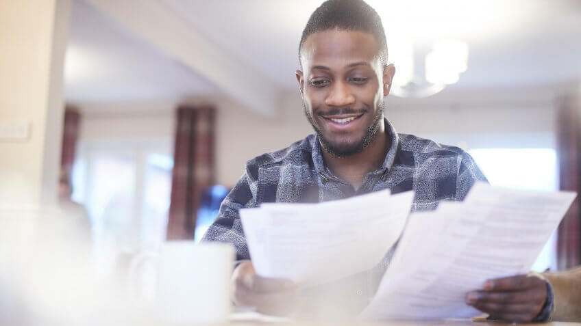 Young black male reading through some paperwork at home.