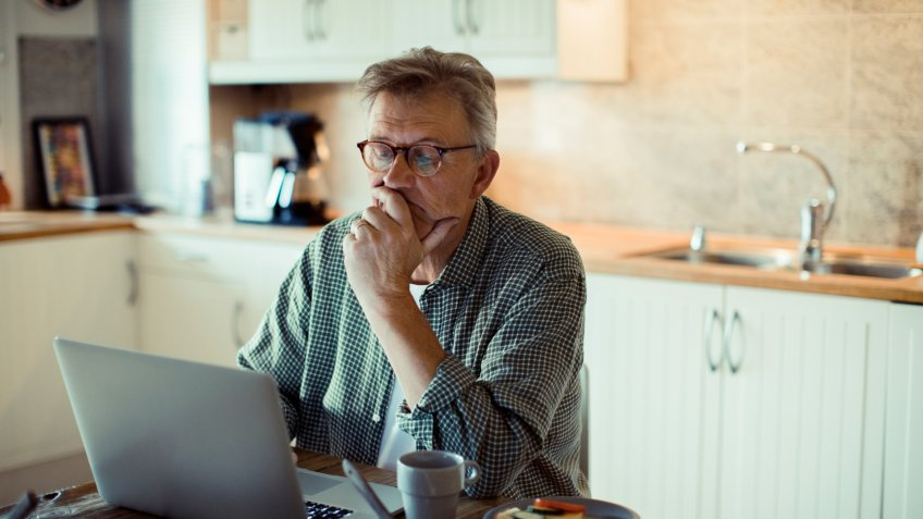 Close up of a mature man using a laptop at home while having breakfast.