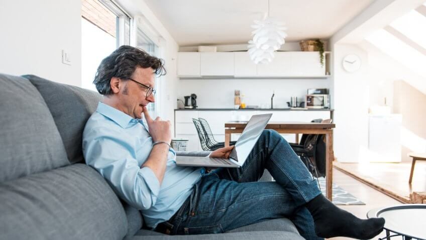 Mature Caucasian man using a laptop and sitting on the sofa in a living room.