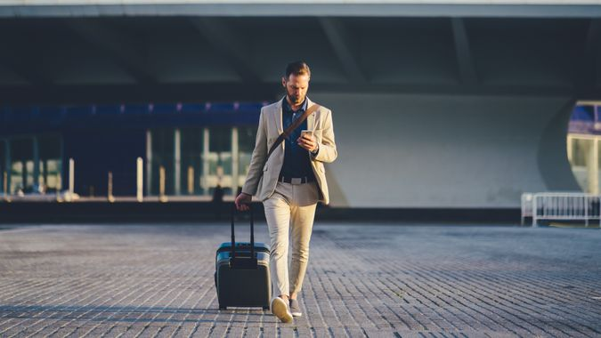 Young businessman with suitcase just arriving in Valencia and texting on phone.
