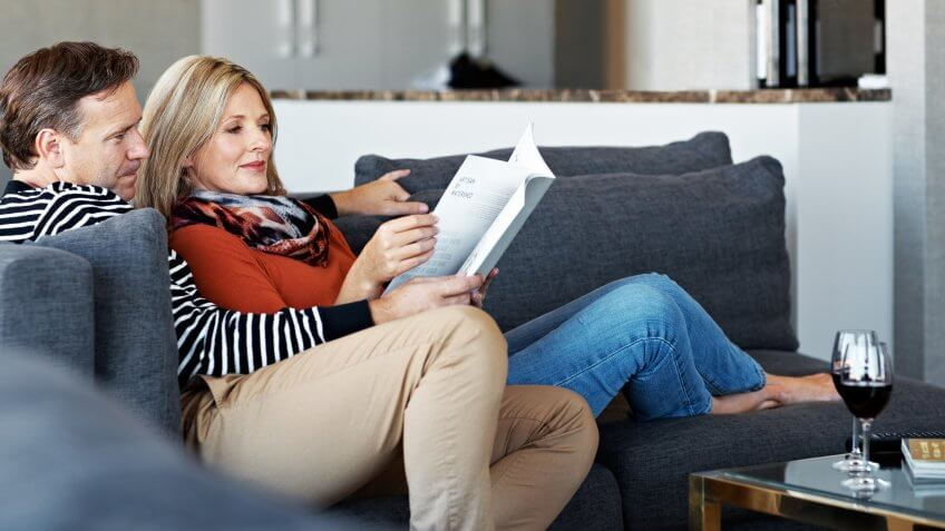 Shot of a mature couple reading a book together on their living room sofa.