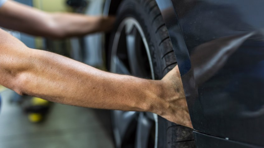 Photo of a young Unrecognizable auto mechanic in uniform is examining a tire while working in auto service.