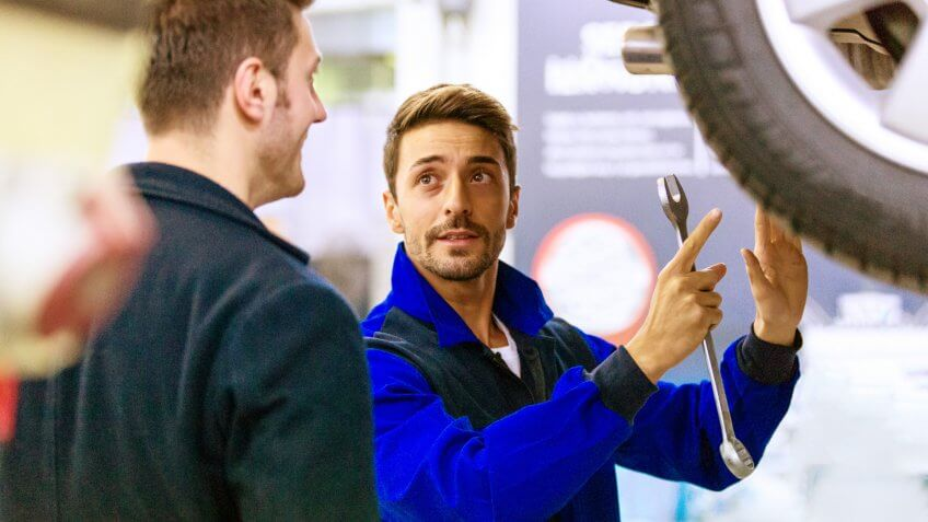 Auto mechanic talking with car owner.