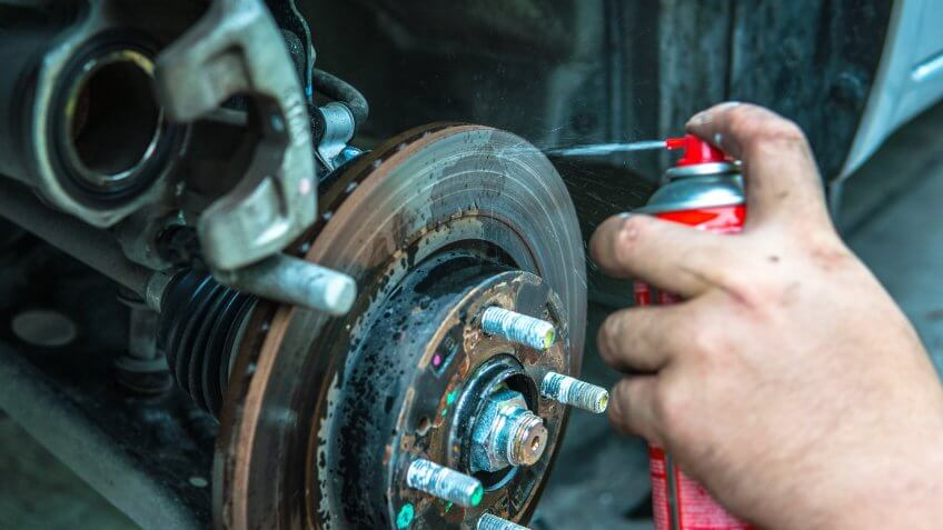 mechanic spraying lubricant on brake rotor