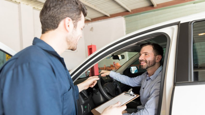 Service man holding clipboard while talking with client in car at auto repair shop.