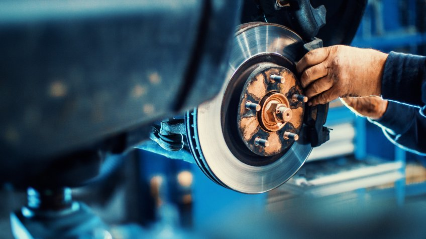 Closeup of unrecognizable mechanic replacing car brake pads.