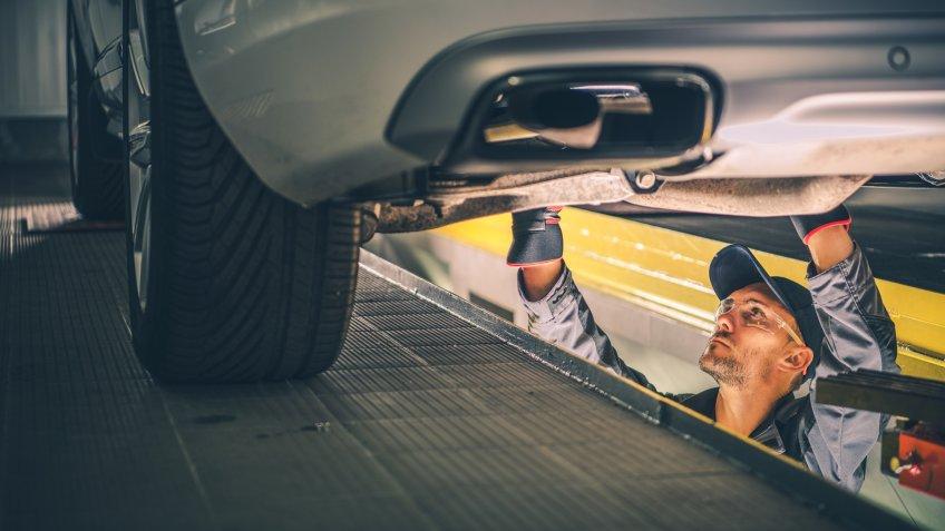 Car Diagnostic Technician Under the Vehicle.