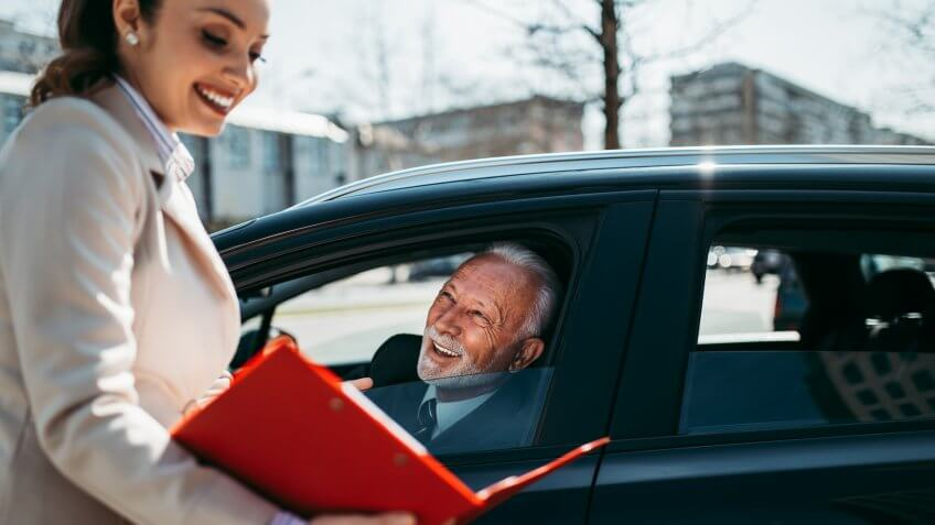 Beautiful young woman sales manager showing car specification to happy senior man buyer.