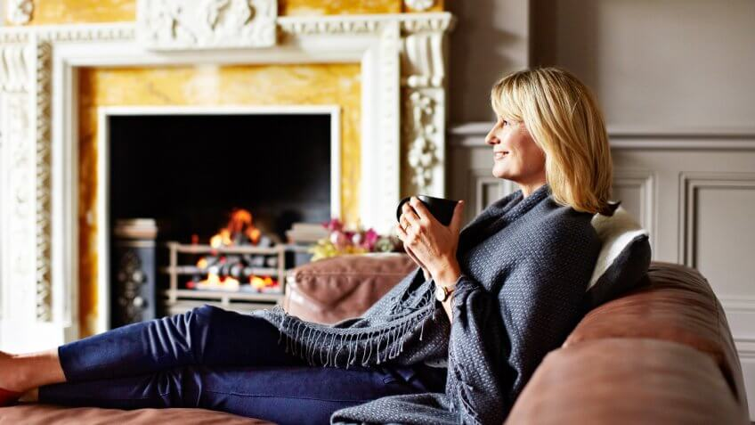 Shot of a mature woman sitting on her sofa drinking tea while wrapped in a blanket.