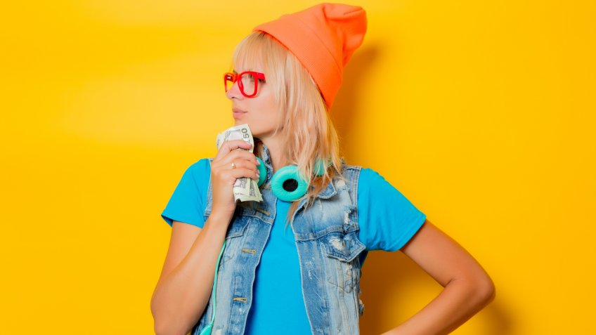 portrait of young trendy girl orange hat with money on yellow background.