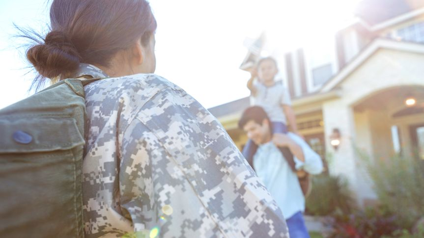 Rear view of mid adult female soldier returning home from military duty.