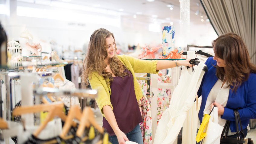 a teenage girl stands in a large clothing store and holds a dress against her mum to show her how nice it is.