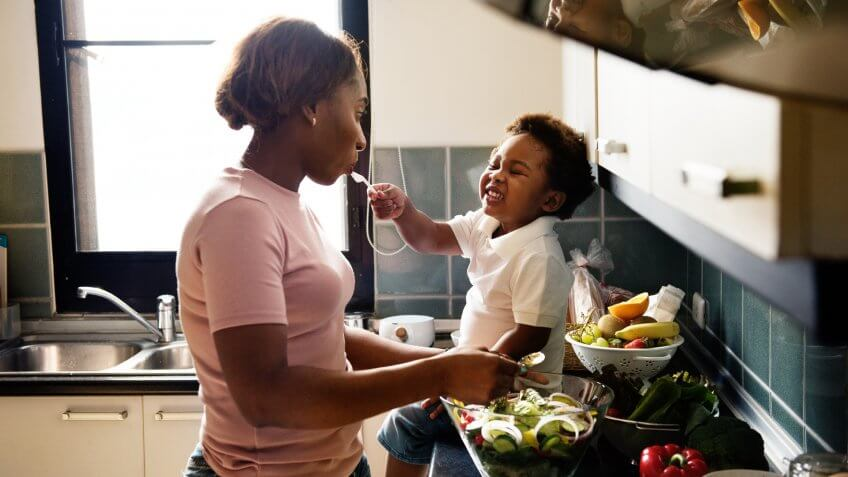 Black kid feeding mother with cooking food in the kitchen.