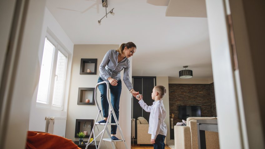 Beautiful mother teaching her young son how to change a light bulb.