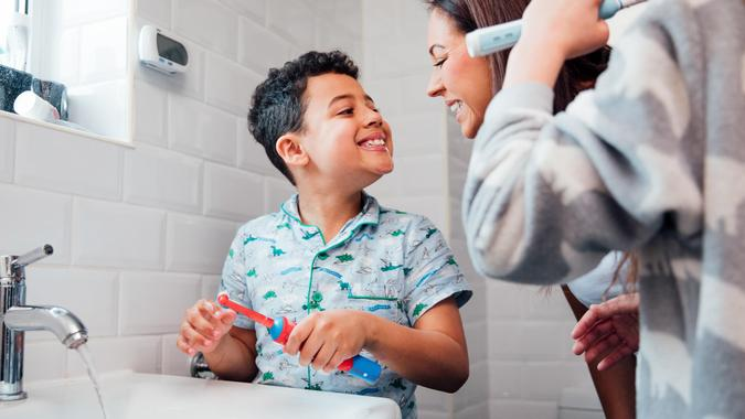 Children are brushing their teeth in the bathroom at home.