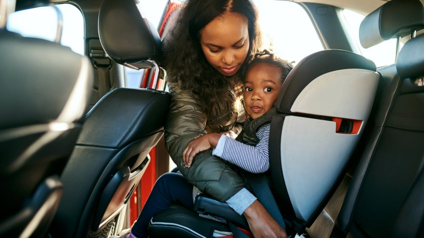 Shot of an adorable little girl being secured in her car seat by her mother.