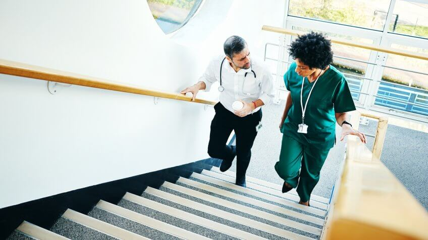 Two medical doctors on staircase having conversation over a case in hospital.