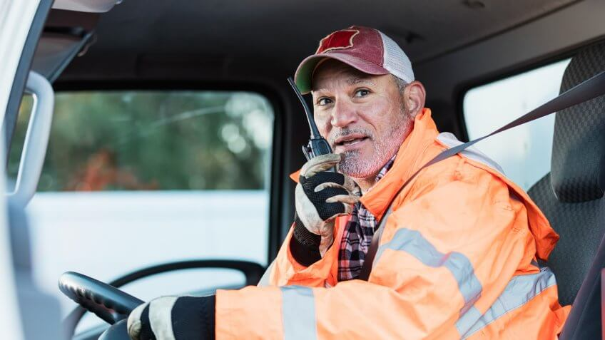 A mature Hispanic man in his 50s, a truck driver, is on his walkie-talkie, sitting in the driver's seat.