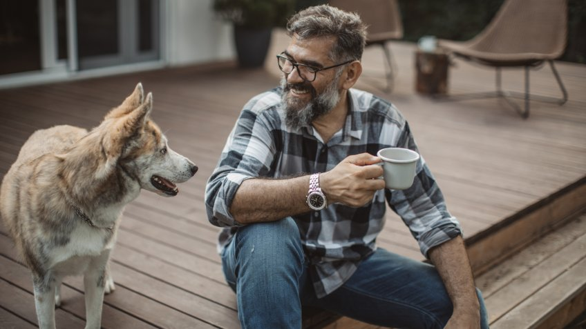 Mature men at his cottage resting on porch with his dog.