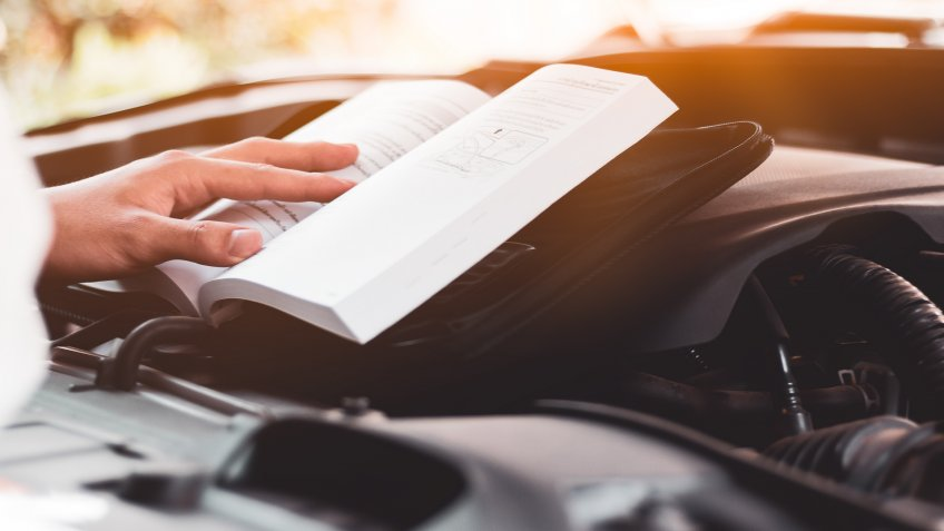 person reading car owners manual