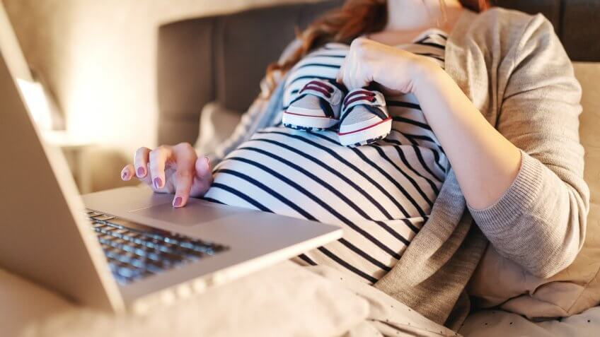 Close up of beautiful pregnant brunette lying in bed, holding baby shoes and using laptop for online shopping.