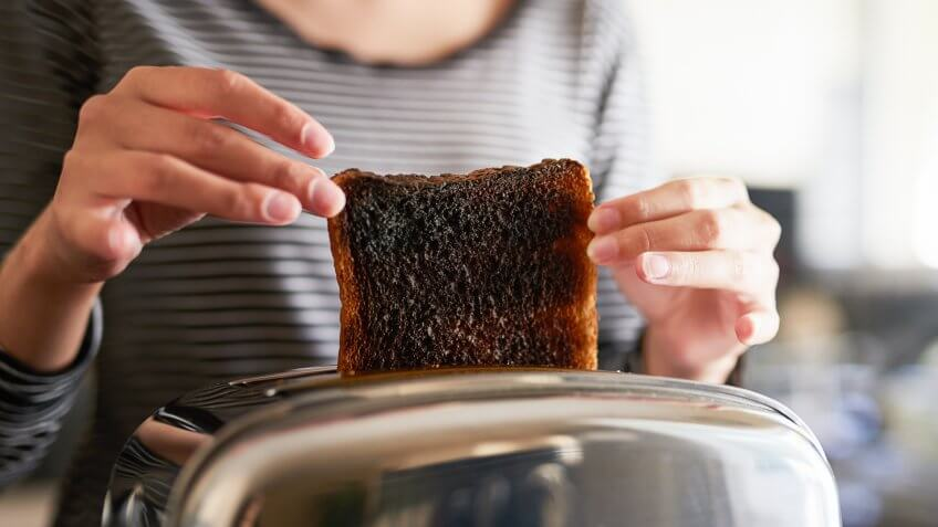 Cropped shot of a woman removing a slice of burnt toast from a toaster at home.