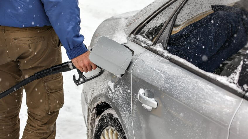 Man holding fuel nozzle, filling gas tank of car covered with snow in winter.