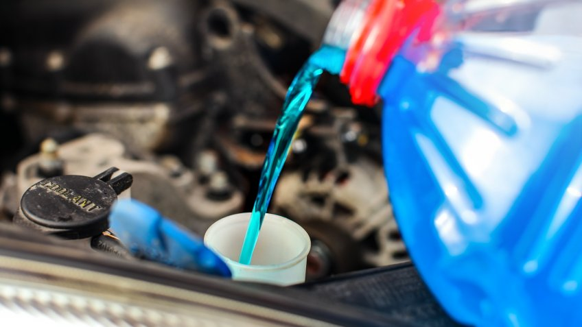 Detail on antifreeze car screen wash liquid pouring into dirty car from blue and red anti freeze water container.
