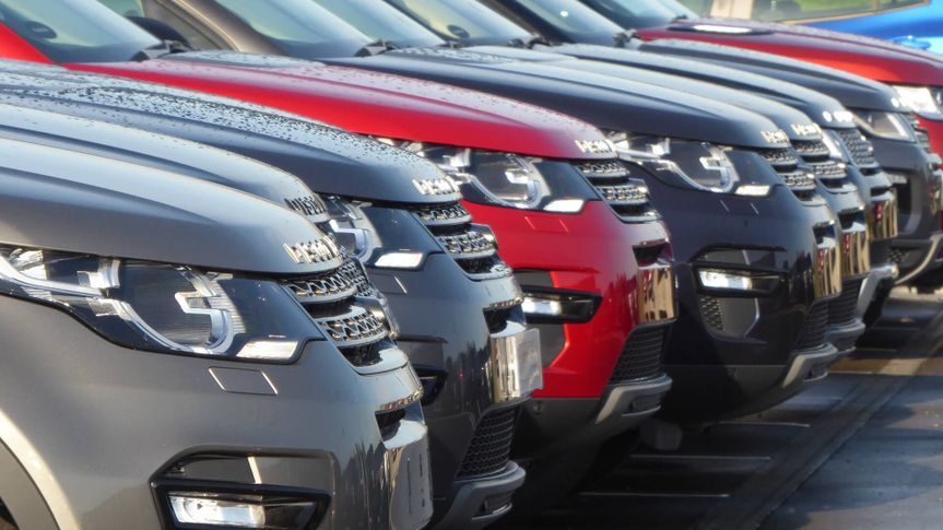 row of new cars in dealership lot