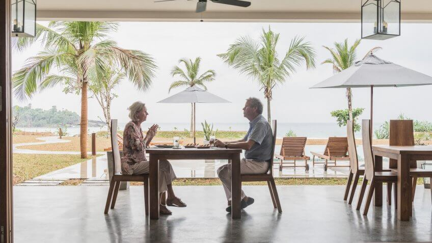 Two people sitting face to face enjoying dinner with view of swimming pool and terrace through open plan room.