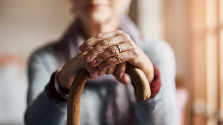 Cropped shot of a senior woman holding a cane in a retirement home.