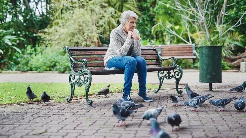 Shot of a senior woman sitting on a park bench and looking thoughtful.