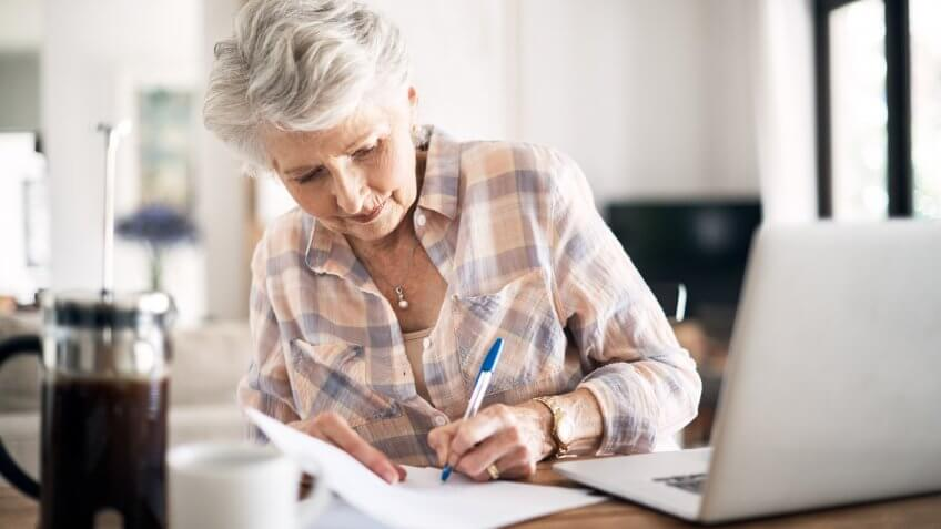 Shot of a happy senior woman flliing in paperwork while using her laptop at home.