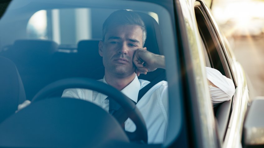 Pensive disappointed businessman sitting in his car and thinking with hand on chin.