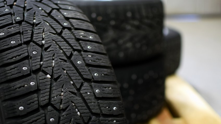 Snow tires with metal studs in garage.