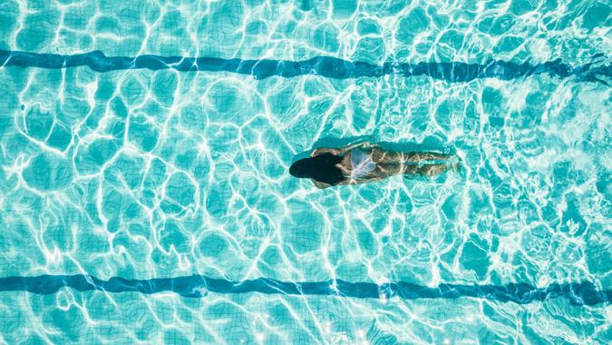 Drone view on teenage girl diving in blue swimming pool.