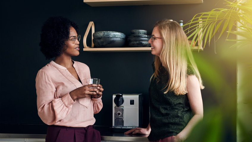 Two diverse female work colleagues smiling and talking while taking a break together in a modern office.