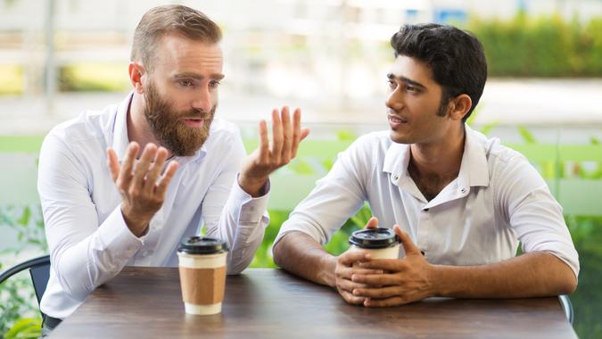 Two male friends drinking coffee and talking in outdoor cafe.