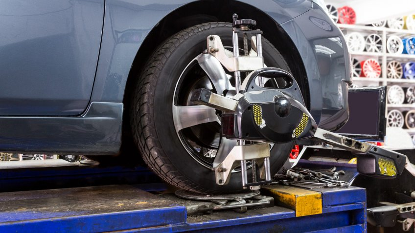 Closeup of tire clamped with aligner undergoing auto wheel alignment in garage.